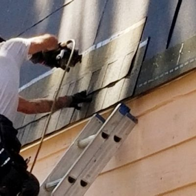 roofer-a-professional-roofer-on-an-extension-ladder-uses-a-pneumatic-nail-gun-to-install-new-shingles_t20_Yw6d44.jpg